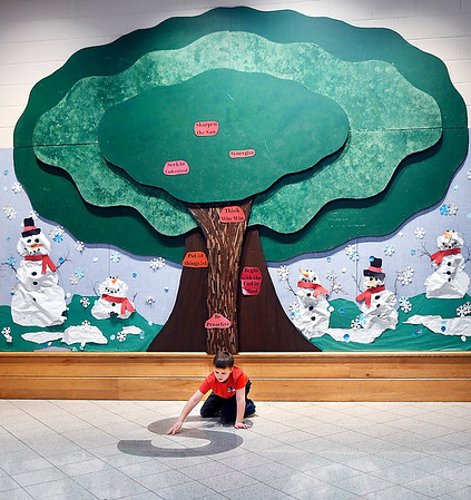 Kellen Graham, 6, a first grader at Frankton Elementary School, outlines the giant S on the floor with his hand as he waits for his classmates from lunch to go to recess under the learning tree in the rotunda area of the school.
