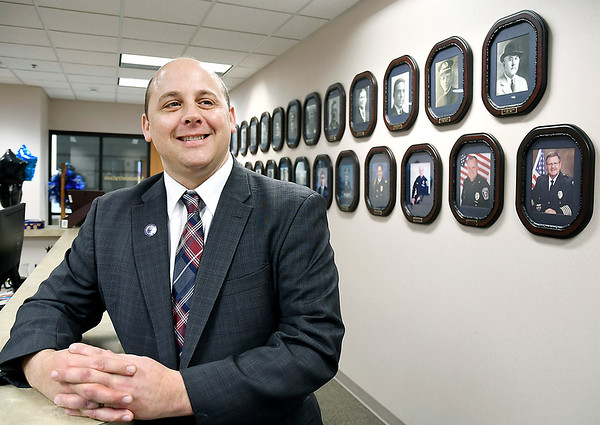 Anderson Police Department Chief Jake Brown with the portraits of all his predecessors in the background in the administration offices of the police department. Brown is one of the youngest chiefs to head up the department.