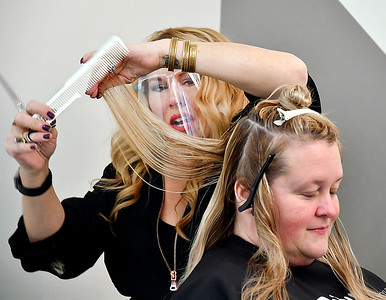 JB Shelton, owner of Detour Salon & Style, works on the hair of client Amy Rayot.