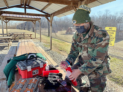 "Joe Katuin loads his paintball gun with pellets before taking part in a boot camp to prepare for ""Operation: Okinawa"" at White River Paintball Saturday in Anderson."