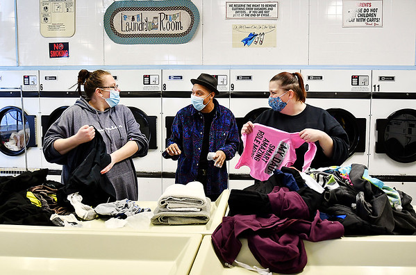 Amanda Gay, left, and Barbara Bolin, right, talk with Rio King while they fold clothes Tuesday at the A & J Laundry in Anderson. King was part of a free laundry day sponsored by the Y Not U Foundation and the Redwood Foundation to help families by paying for up to three loads of laundry and supplying free detergent, bleach and fabric softener also.