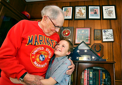 World War II veteran Carl Scott, 97, gives his new best friend, Christian Robison, 9, a hug as they visit at Scott's Elwood home recently. Robison is interested in the military, the flag and and all things American, and with Scott's knowledge and experience has taught Christian a great deal about our country.    Christian Robison, 9, with his new best friend, WWII Marine veteran, Carl Scott.