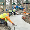Workers from DC Construction smooth out the fresh concrete of a section of the new walkway that will wrap around the playground equipment at Shadyside Park Wednesday. This is part of the contract work approved by the Anderson Parks & Recreation Board for improvements to the playground area.