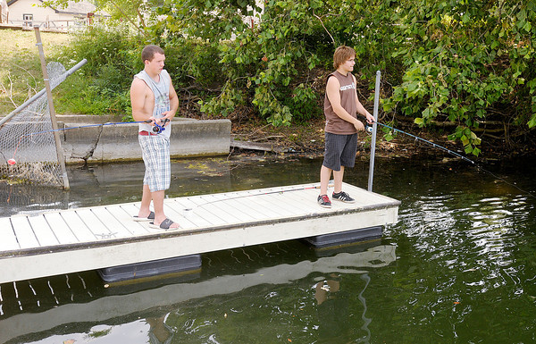 From left, Brandon Coble, 17, and Michael Devol, 16, fish off the dock in front of the Shadyside Bait Shop on Saturday. To cope with the heat anglers are fishing later in day.