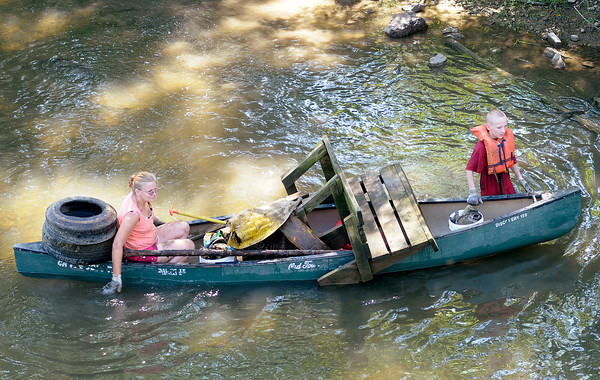 Participants in the White River Watchers River Celebration load their canoes with trash found along the river from Edgewater Park to Riverbend Park on Saturday.