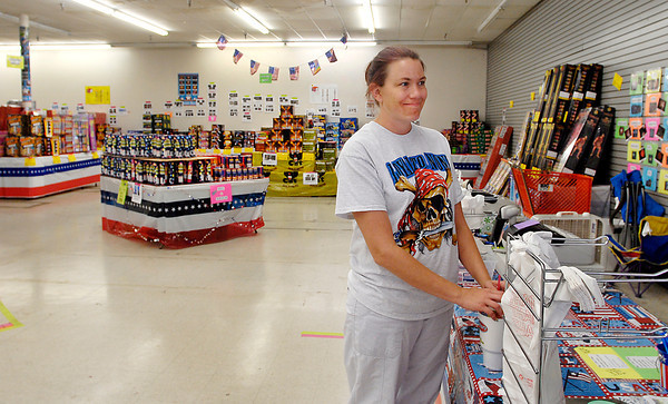 Tammie Denning waits patiently for customers at the USA Fireworks store on south Scatterfield Road Tuesday afternoon.  Business has fallen off since the talk of a possible ban on fireworks in the area.