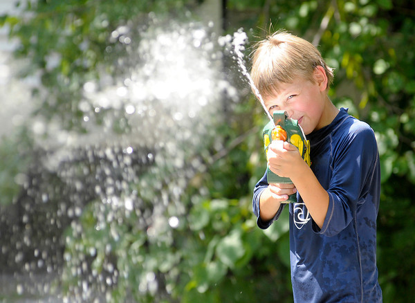 Daniel Lindenlaub, 11, from Osceola, keeps cool with water guns while camping at Mounds State Park on Saturday.