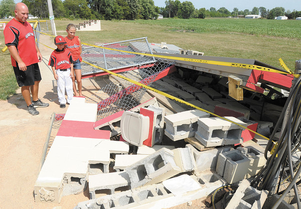Brad Douglas and his kids, Sydney, 11, and Bradyn, 7, look at the pile of rubble that was once a dugout on the field used by Frankton Coaches Pitch on Thursday. One dugout was leveled and the other was damaged by high winds during last Friday's storm. Several volunteers have come forward to help replace both dugouts now the league needs donations to help cover the cost of materials. Donations can be made by contacting Mindy Lapierre at the PNC branch in Frankton.