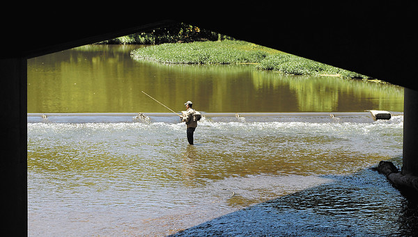 Framed by the Truman Bridge this angler tries his luck fishing along the spillway just up stream from the bridge.