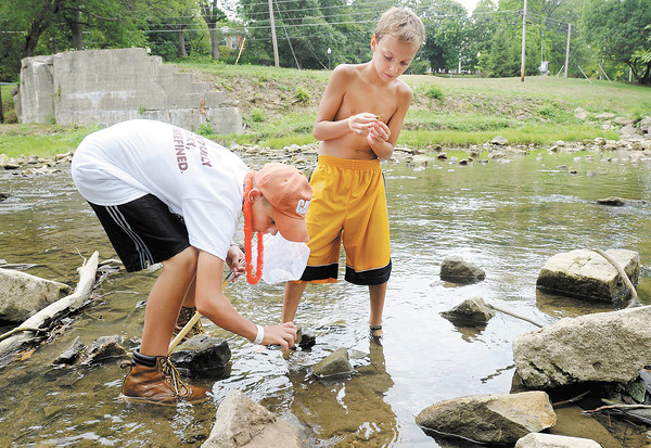 From left, Shane Haygood and Nathaniel Soultz search under rocks for crawfish in Fall Creek on Thursday.