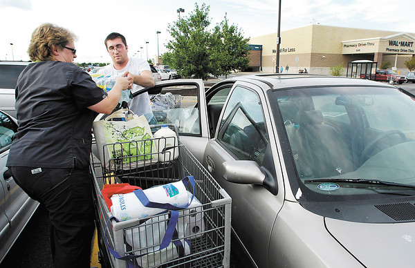 Hedy Bandy passes items to her son Keith Woodcock as he loads up the car after they did their grocery shopping with two full carts at Wal-Mart Friday evening.