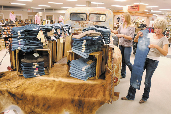 Marla Stanley and Molly Judd fold jeans at Cowpokes on Thursday. Cowpokes at Exit 26 is one of many businesses to be affected by INDOT's renumbering of I-69.