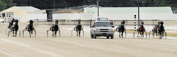 Drivers lined up behind the starter for the final night of  live standardbred racing at Hoosier Park Saturday evening.