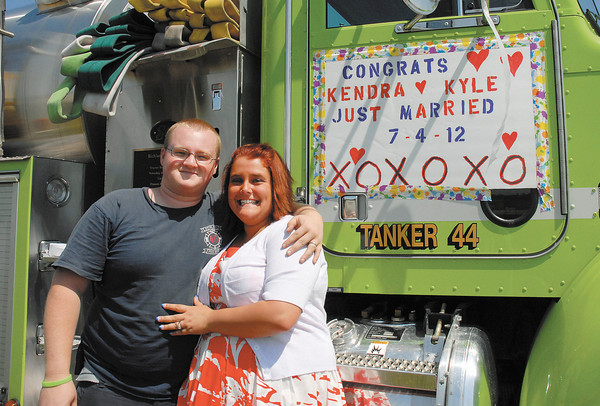 Newlyweds Kyle and Kendra James stand by Richland Township's Tanker 44 before riding in the Chesterfield Independence Day Parade on Wednesday. Kyle and Kendra were married earlier in the morning making Kyle the third generation from his family to wed on Independence Day.