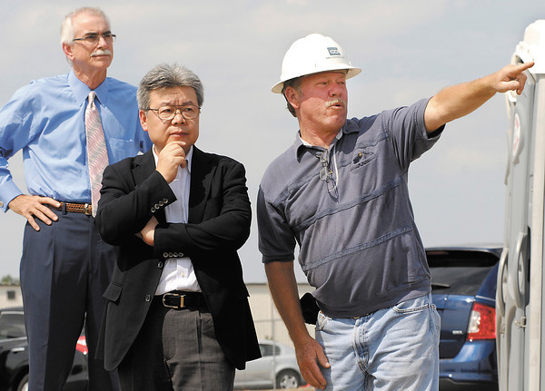 Steve Adams, right, construction superintendent for GDI Construction, points out to Hiroyuki Omori, executive managing officer for Moriroku Technology Co., the parent company of GTI, some of the features of the site as David Bunting, background, president of GDI Construction, looks on.
