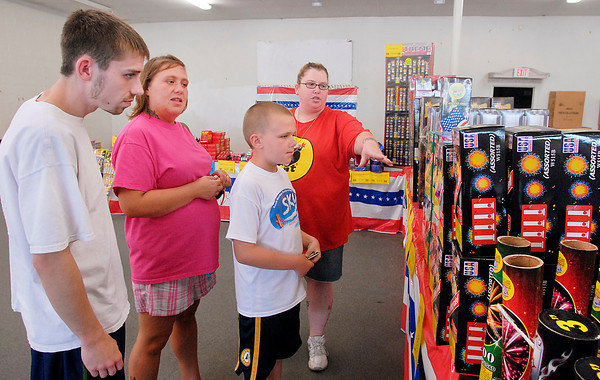 Rachael Rutledge, right, of USA Fireworks, shows customers Ian Gick, Latichia Turner, and Leethan Turner, 10, the different types of fireworks they have for sale at their east 53rd Street location Tuesday afternoon.