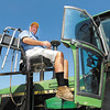 Paralyzed farmer Mark Hosier uses an electric lift to get into his tractor.