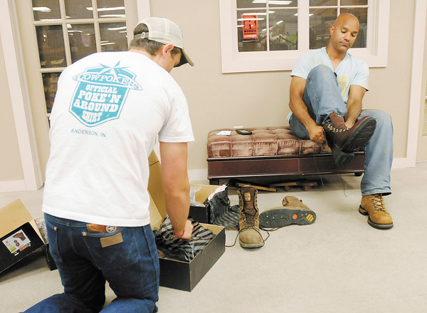 Cody Earlywine, left, helps Kenny Brown pick out a pair of work boots at Cowpokes on Thursday. Cowpokes at Exit 26 is one of many businesses to be affected by INDOT's renumbering of I-69.