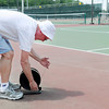 Jim Dixon uses speaker wire to set up the public announce system at Anderson University for the Community Hospital Anderson Tennis Classic Friday afternoon. The tournament starts on Saturday and Dixon will be competing in four different divisions.