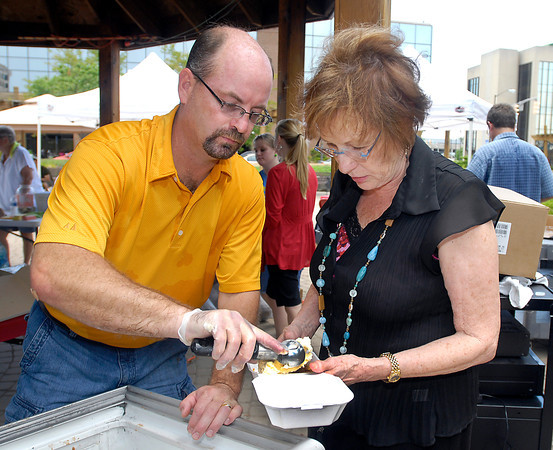Rob Hayes, Anderson Center for the Arts board member, scoops up some ice cream for Linda O'Neill's cake during the art center's ice cream social Wednesday at Citizens Plaza Park.
