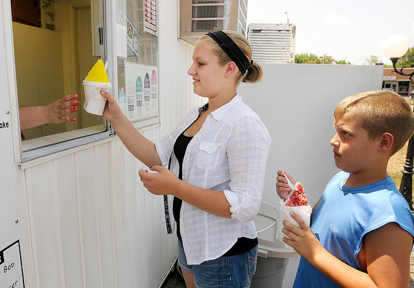 From left, Hannah and Ethan Hauk keep cool with snow cones from Sno-Castle on Broadway on Friday. Anderson residents dealt with triple digit heat on Friday, a trend that is expected to break after a cold front arrives over the weekend.
