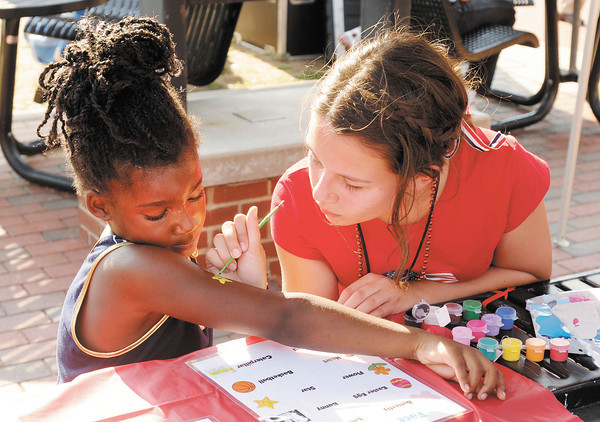 Grace Stottlemyer paints a star on five-year-old Karter Horne's arm during the Freedom Fest at Town Center Park on Wednesday. The event was sponsored by Celebration Church at Arrow Heights, Madison Park Church of God and South Meridian Church of God.