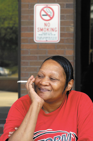 Mary Poole enjoys her last day to smoke in the outdoor designated smoking area at the Madison County Government Center Friday.  With the new state-wide smoking ban taking effect July 1 there will be no smoking on the property. Poole works in Circuit Court 5.