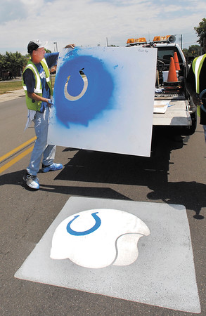 Mark Davis, of the Anderson Street Dept., paints horseshoes on helmets along University Blvd. Friday.  The city is prepping for the opening of Colts training camp with 65 Colts helmets painted in the street from Scatterfield to Nursery Road.