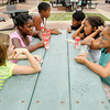 Clockwise from left, Hannah Whipple, Jonae Grabes, Ty Lawler, Mandel Hunt, Makailyn Stewart, Jayce Newsom eat their afternoon snack at the Town Center Park during the YMCA's summer camp on Tuesday.