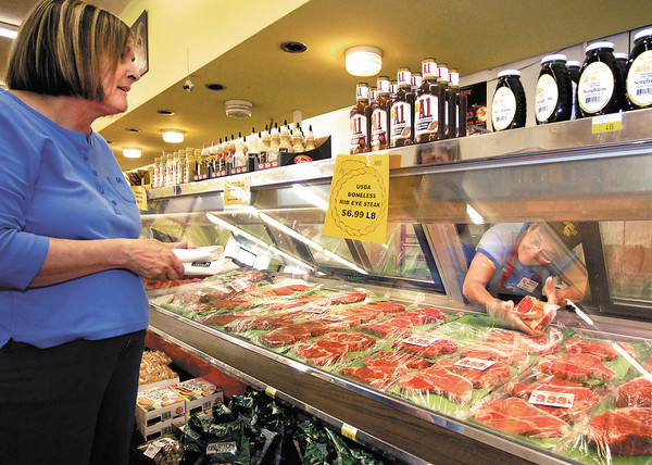 Lynn Fredericks , right, shows shopper Betty Irwin different rib eye steak cuts at the Harvest Supermarket at 8th & Scatterfield Road.