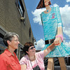 """Zola Noble and Kim Ousley are """"yarn bombing"""" all the Walking Man statues around Anderson.  Here they have placed their knitted arm band on the statue that is out front of Gray's Design Studio at 14th & Main Streets."""