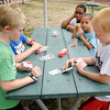 Jaydon Laycock and Eli Michalek play the card game war during YMCA's Summer Camp on Tuesday.