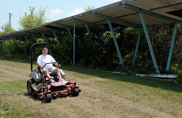 Dan Nolan of Crossroads United Methodist Church mows grass at the former Boca Real golf course. The church maintains the property and has purchased five acres of the former golf course and plan to install a prayer walk.
