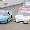 Don Knight/The Herald Bulletin<br /> Eddie Van Meter (23) takes the lead from Ross Kenseth (25) while Johnny VanDoorn (61) is in third on a restart during the Stoops Freightliner Redbud 300 at the Anderson Speedway on Saturday.