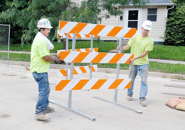 Don Knight/The Herald Bulletin<br /> Construction workers move road barriers as work continues on West 3rd in Anderson. Those working outside are dealing with 90 degree heat this week.