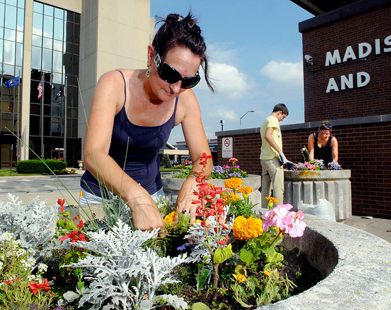 People from the  Community Justice Center weeding the flowers in the large pots around the Madison County Government Center.