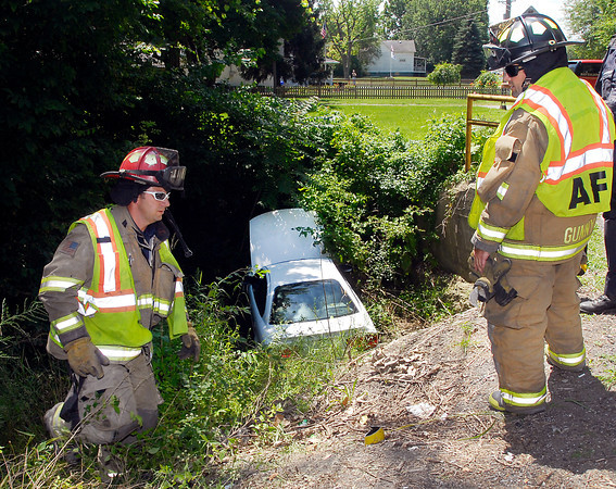 Anderson Fire Department personnel climb up out of a deep drainage ditch in the 1400 block of Alexandria Pike after this vehicle drove off the road and into the ravine Friday afternoon.