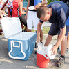 Don Knight/The Herald Bulletin<br /> Jacob Rowan, 17, reloads his water cooler with fresh ice as the Anderson High School marching band practiced in the parking lot Thursday evening. Band parents supplied fresh ice, students took frequent water breaks and the band moved their outdoor practice to the evening to combat Thursday's heat and humidity.
