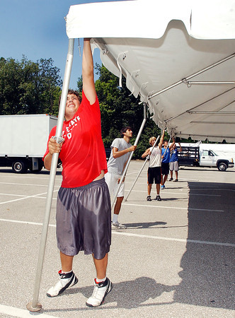 Max Johnson, along with his co-workers, raise the tent their setting up Tuesday at Anderson University.  They work for All Occasion Tent Rental, Inc. of Greenwood, Ind. who was busy raising canvas for what will become Colts City at the Indianapolis Colts Training Camp starting this Sunday.