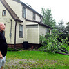 Lester Osborne looks at the tree from which a large section was blown out and into his house doing damage.  Osborne lives on CR 700 West near Lapel.
