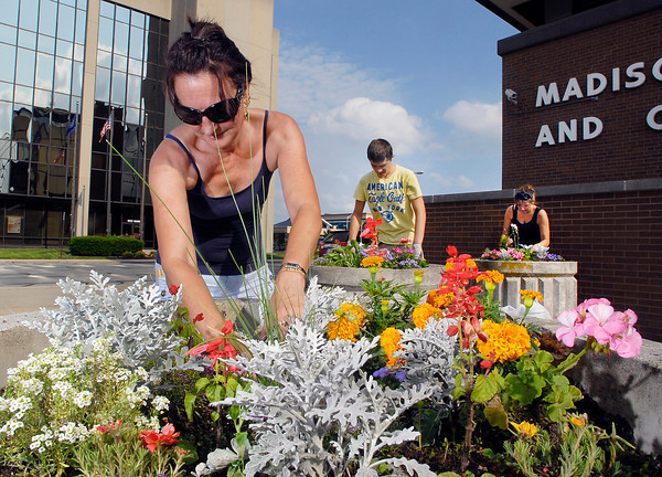 Christi Tyner, from the Community Justice Center, with help from Zack Herndon and Hollie Muzik, pull the weeds from the large flower pots that surround the Madison County Government Center Monday evening.  The Community Justice Center adopted the planters and the employees plant and maintain the flowers for the county.<br /> <br /> <br /> <br /> People from the  Community Justice Center weeding the flowers in the large pots around the Madison County Government Center.