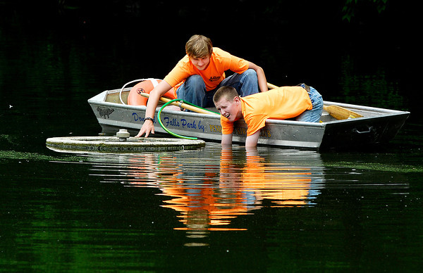 High School students Tristan Gray and Riley Cochran work from a boat as they disconnect the connections to the fountain in the pond at Falls Park in Pendleton to replace the pump.  The two are working the summer for the Pendleton Parks Department.