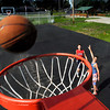 Dayton Elsworth, 15, follows his shot as his brother Noah, 13, defends him as they play basketball on the newly renovated courts, including all new goals, in Callaway Park in Elwood.  The city has done many improvements to the park in recent weeks.