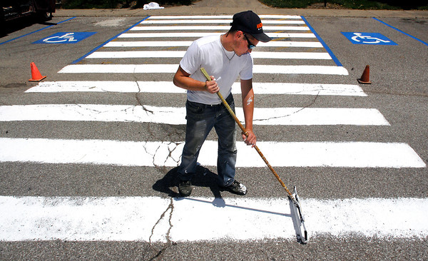 JB Bilbrey paints the stripes of the cross-walk that crosses Colts Way on the Anderson University campus Friday afternoon.  The university is preparing for the start of Colts camp later this month.