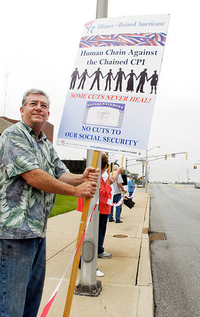Ted Hensley, of Anderson, holds his sign up as he and a group of seniors demonstrated along 8th Street in front of the city building Tuesday protesting the proposed changes to their Social Security benefits.