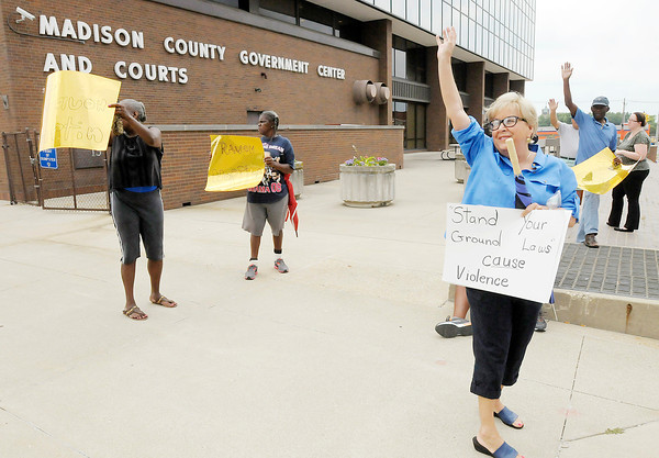 """Don Knight/The Herald Bulletin<br /> The group Friends of Trayvon wave at a passing motorist who honked in support as the group protested """"Stand Your Ground"""" laws outside the Madison County Government Center on Saturday."""