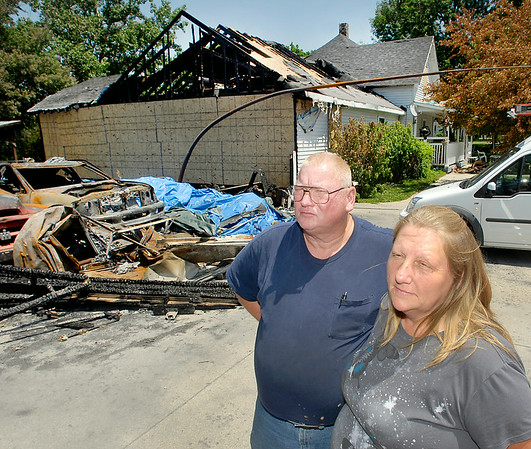 John P. Cleary | The Herald Bulletin<br /> Dewayne and Tina Presley look over the burnt out remains of their Summitville home where they lost items of memories of the almost 300 people that lived in that house over the 16 years the Presleys ran a foster program that touched the lives of many children over the years.