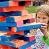 "John P. Cleary | The Herald Bulletin<br /> Khloe Baugher, 9, tries her skills at the oversized ""jenga"" game during the Greater Light Churchs'  Greater Light Gives Back event held Saturday.  Players  won tokens for their efforts and then could trade those in for prizes of school supplies."