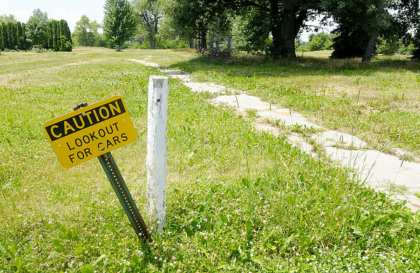 Don Knight   The Herald Bulletin<br /> A caution sign warning golfers to look out for cars stands next to the cart path where it crosses Fairway Drive at the Yule Golf Course in Alexandria. Neighbors are upset with the condition of the former course.