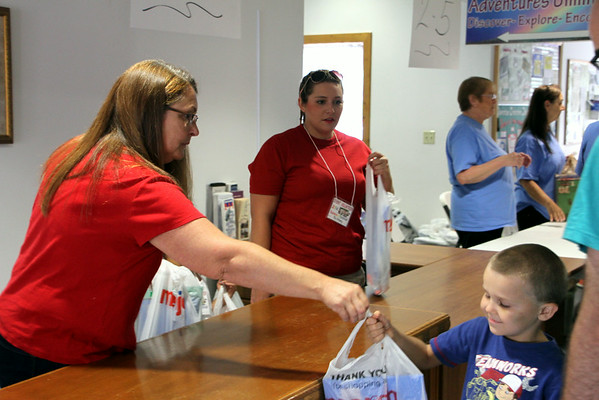 Chris Martin for THB<br /> Volunteer Tammy Norrod hands out supplies to children at the school supply giveaway sponsored by the Anderson Parks Department held at Mounds Baptist Church Sunday